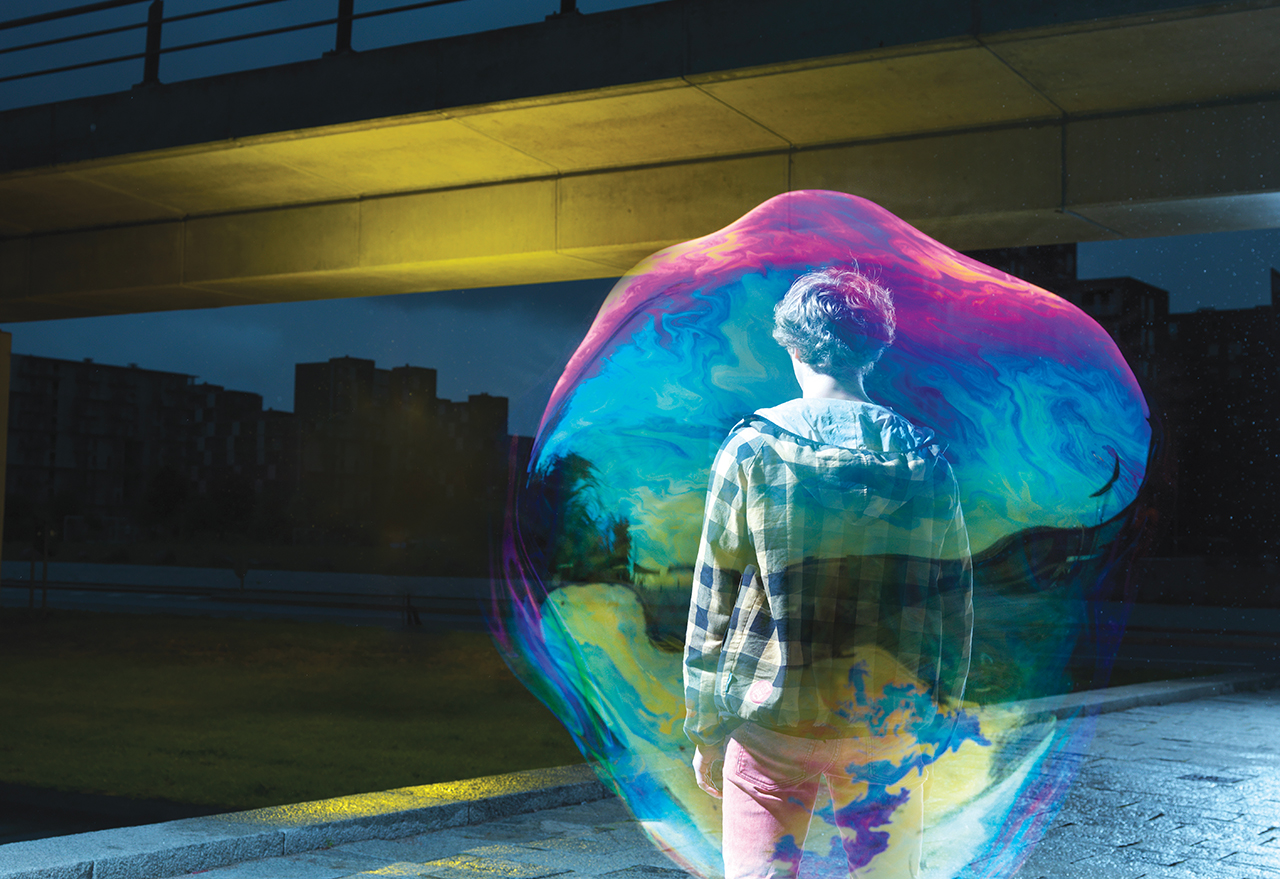 photo illustration. a young white man in a hoodie is seen from the back in a city at night. he is enveloped and obscured by a multi-colored bubble.