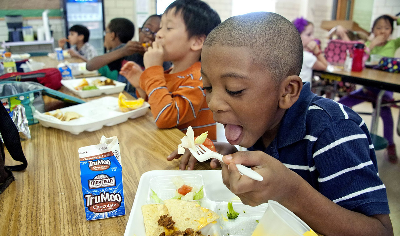a young Black boy puts a fork of broccoli into his mouth