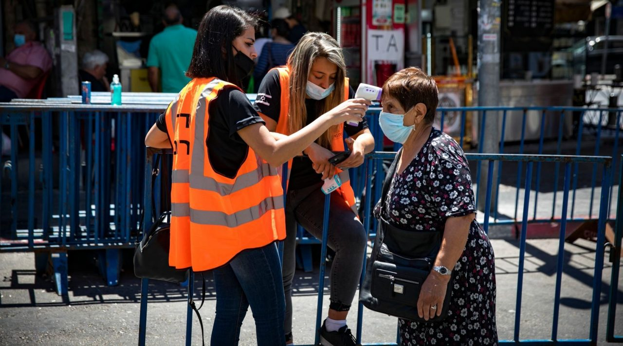 An Israeli woman has her temperature taken before entering the Mahane Yehuda market in Israel, June 16, 2020. (Photo/JTA-Olivier Fitoussi-Flash90)