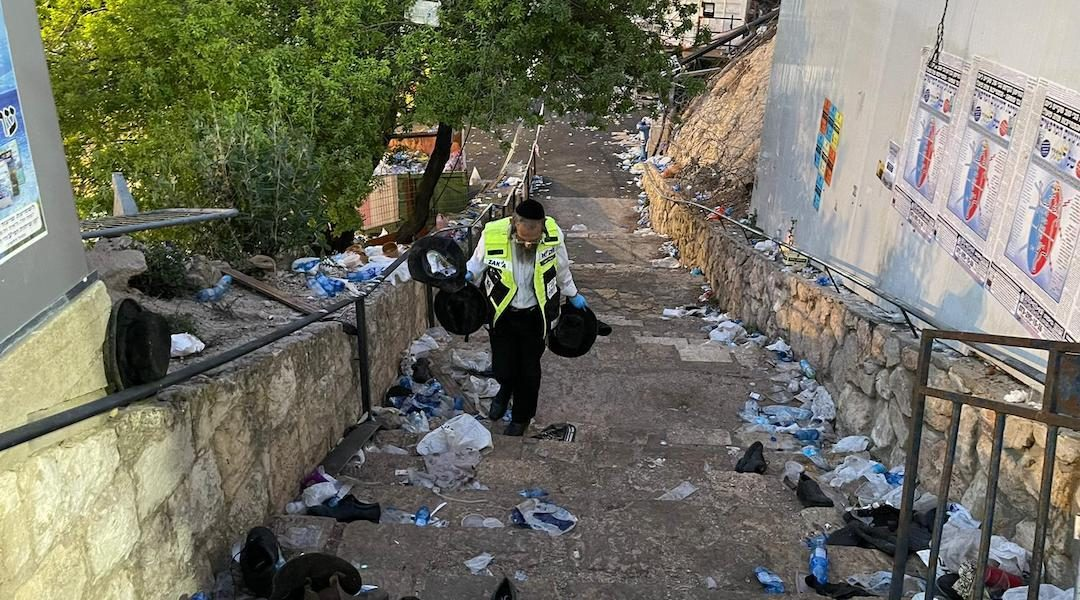 man walking up stairs covered in debris, trash and garments