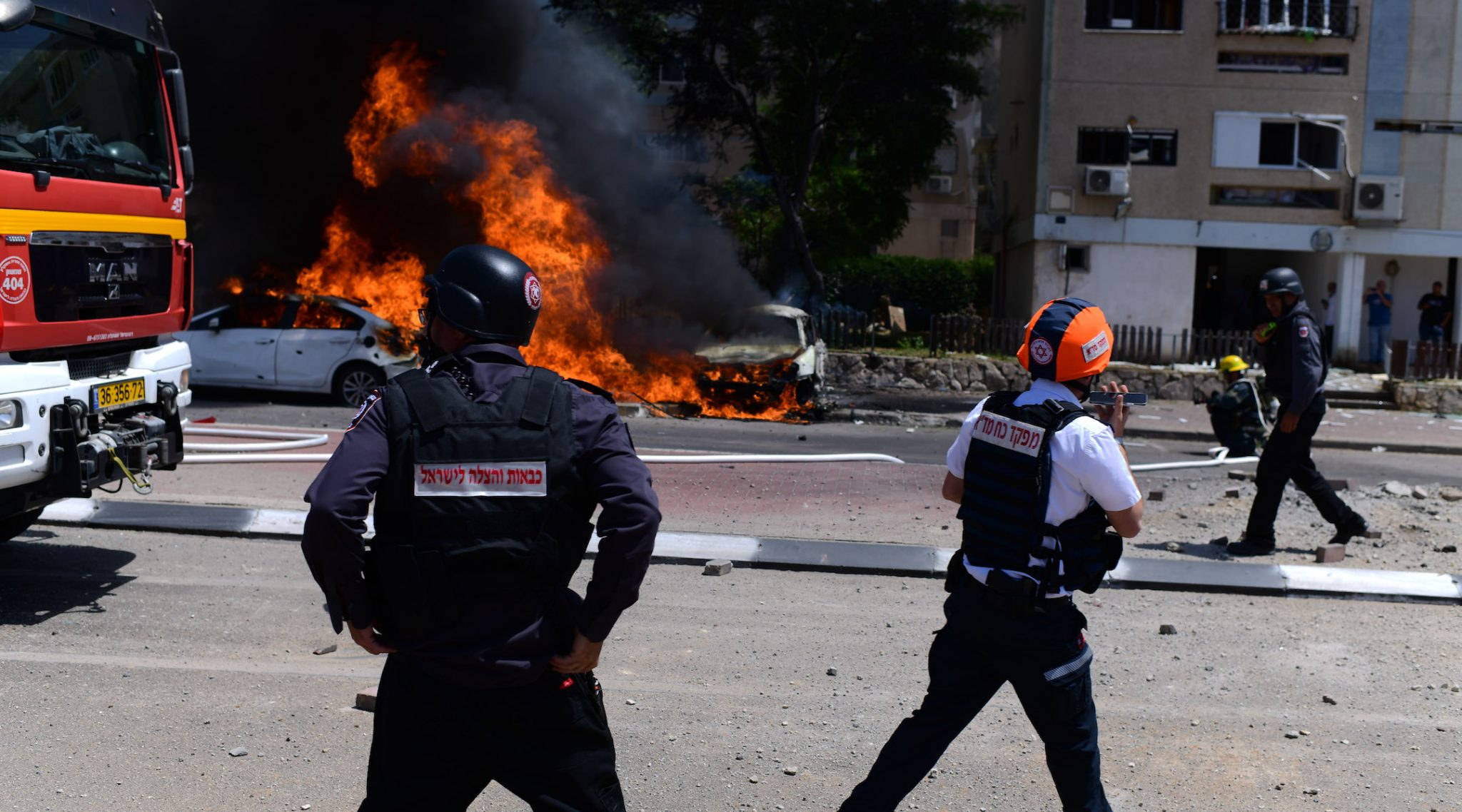 An Israeli firefighter extinguishes a burning car after a rocket fired from the Gaza Strip landed in the city of Ashkelon, May 11, 2021. (Photo/JTA-Tomer Neuberg-Flash90)