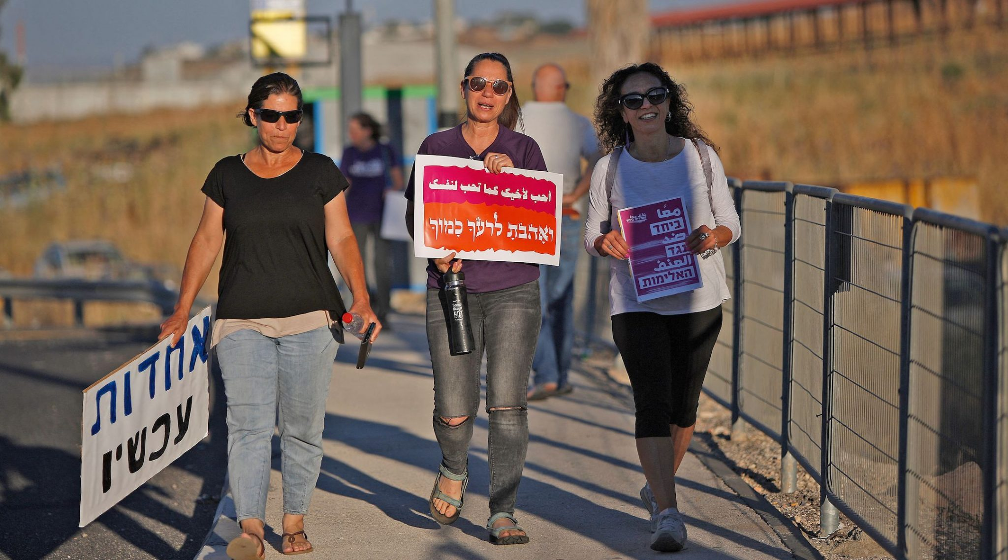 three middle-aged women walk down a sidewalk holding signs in hebrew and arabic