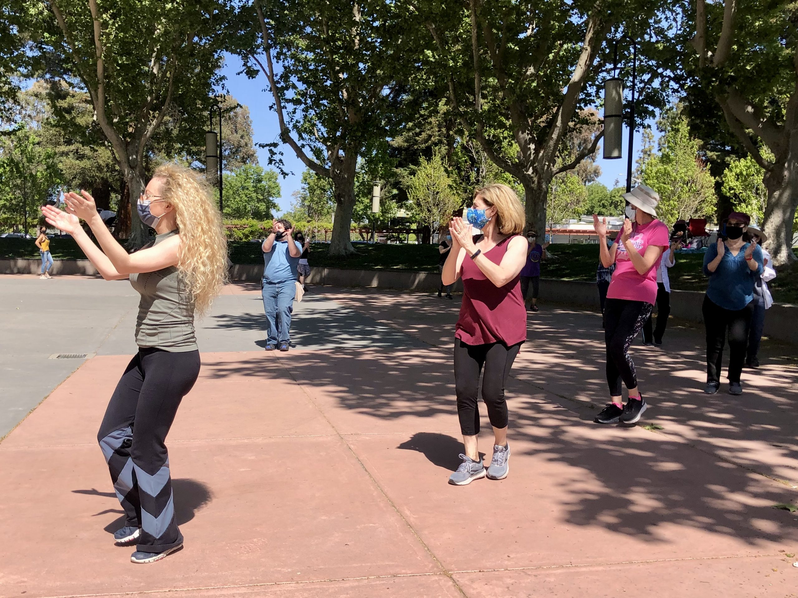 Aaron Alpert, in blue, leading an Israeli dance session at Palo Alto's Mitchell Park earlier this month. (Photo/Andrew Esensten)