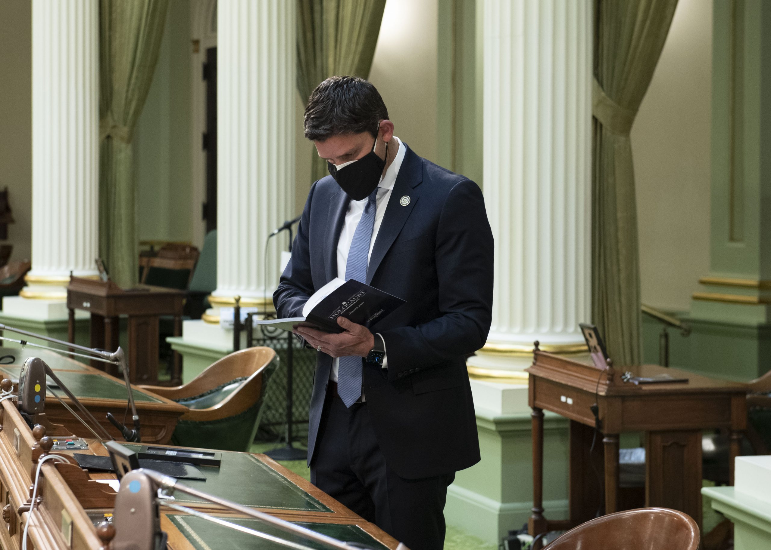 man in suit with mask reads book in state capitol chamber