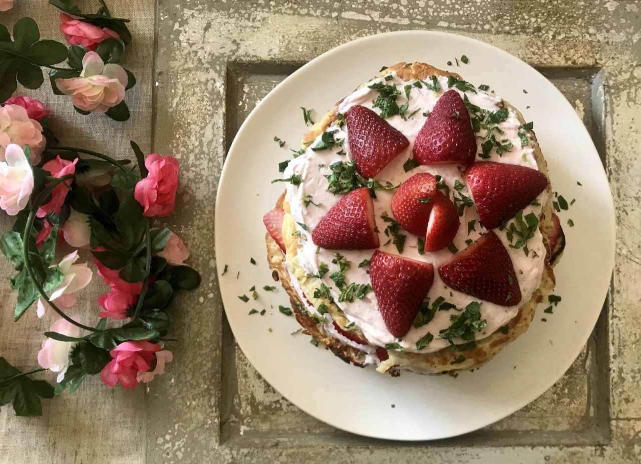 plate with pancakes and strawberries next to fake flowers