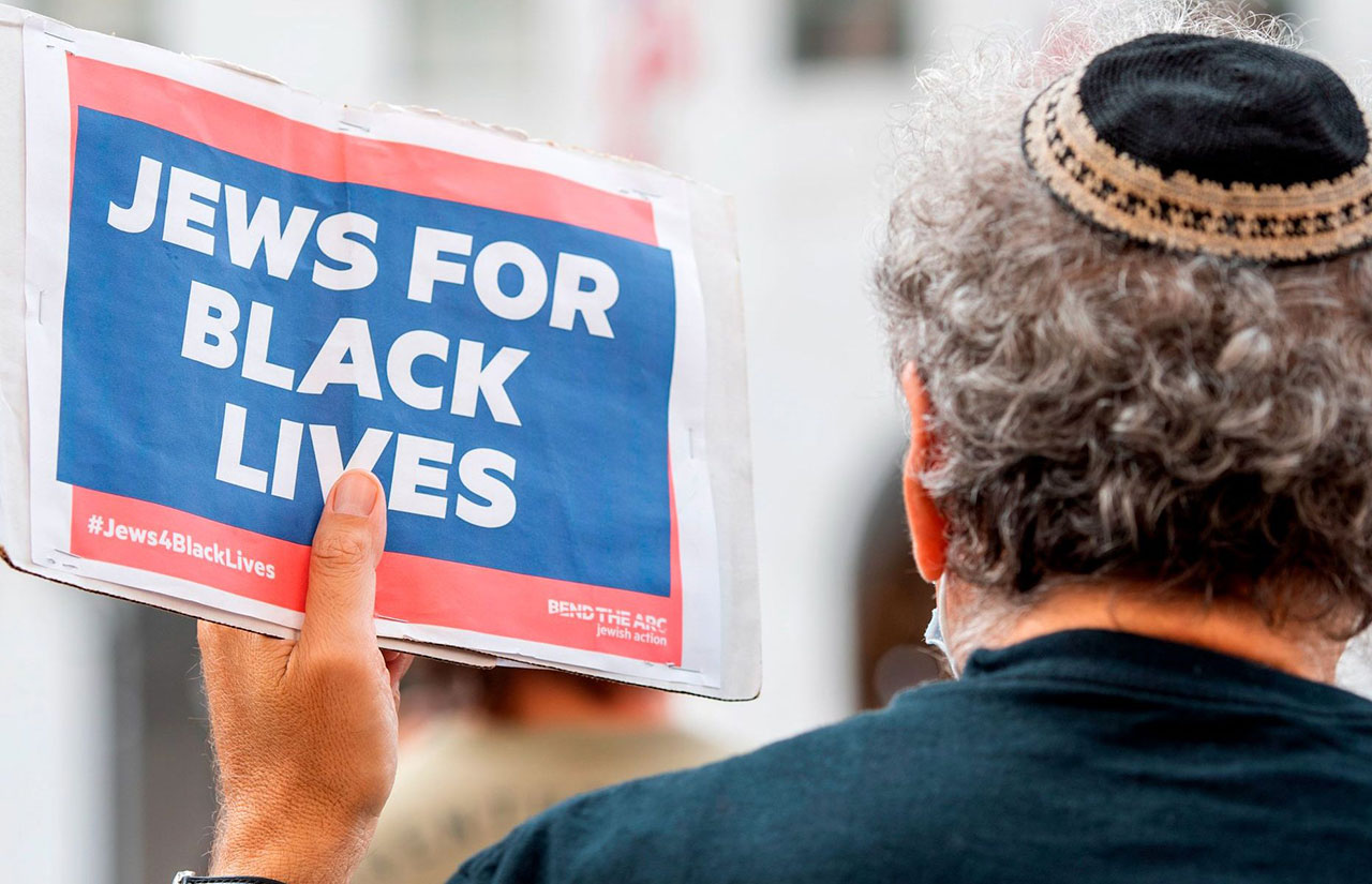 """A kippah-clad man holds a sign reading """"Jews for Black Lives"""" at a Black Lives Matter protest in front of the Hall of Justice in Los Angeles, Sept. 9, 2020. (Photo/JTA-Valerie Macon-AFP via Getty Images)"""