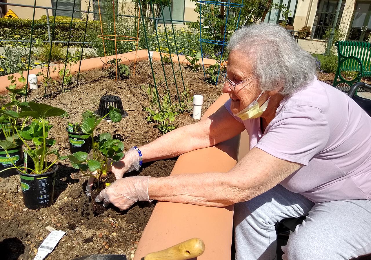 A resident of Reutlinger Community works in the new Deborah L. Lind Memorial Garden.