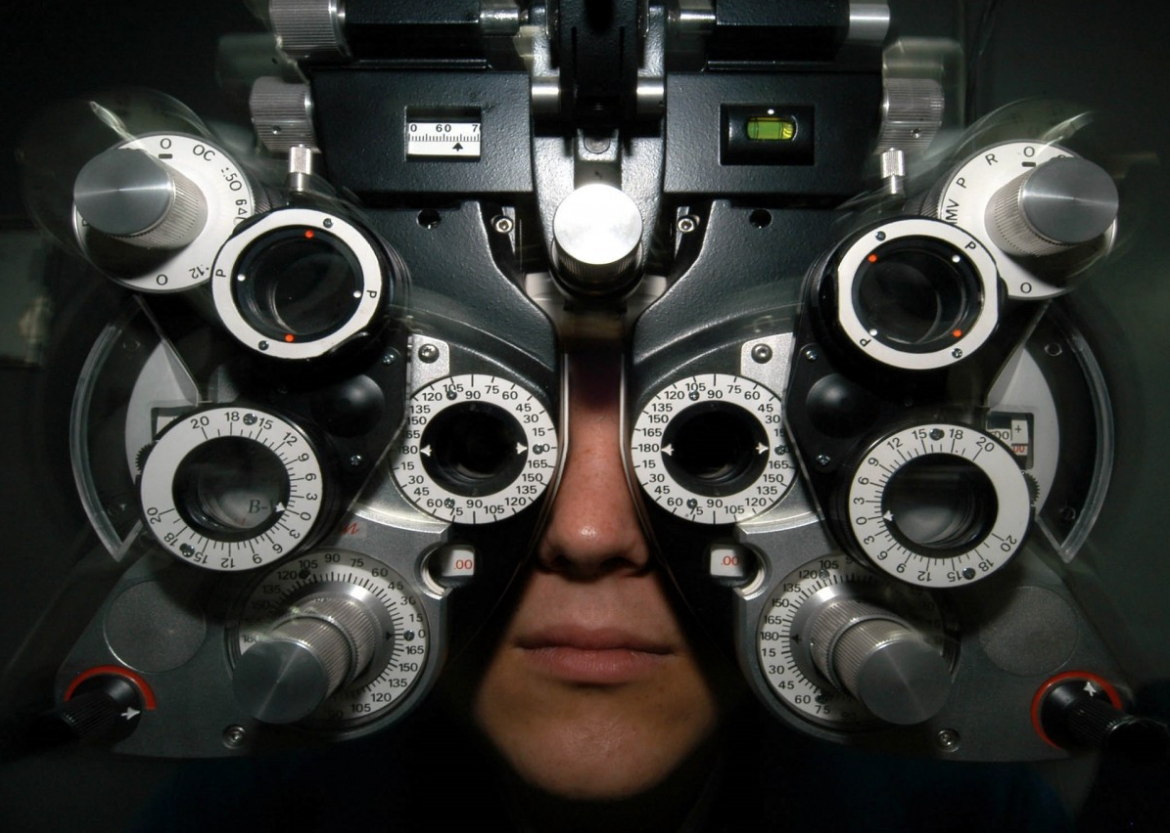 A person's face pressed up against a piece of optometry equipment.