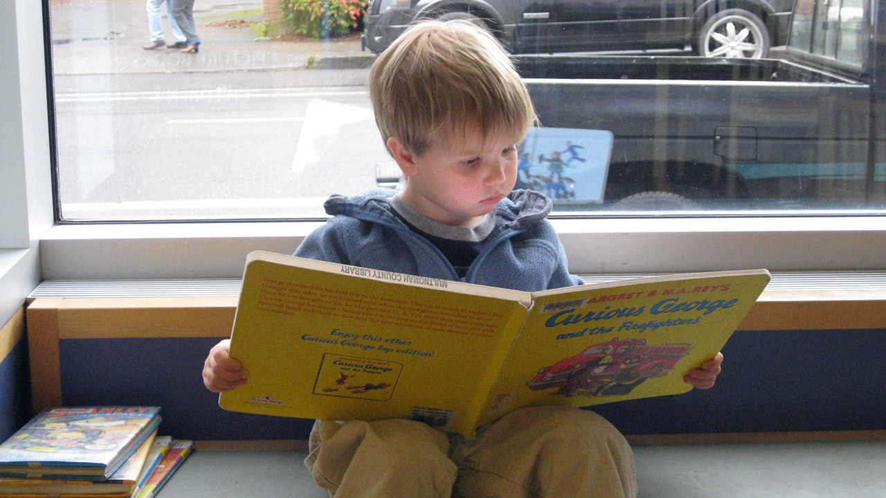 a young boy sits reading Curious George
