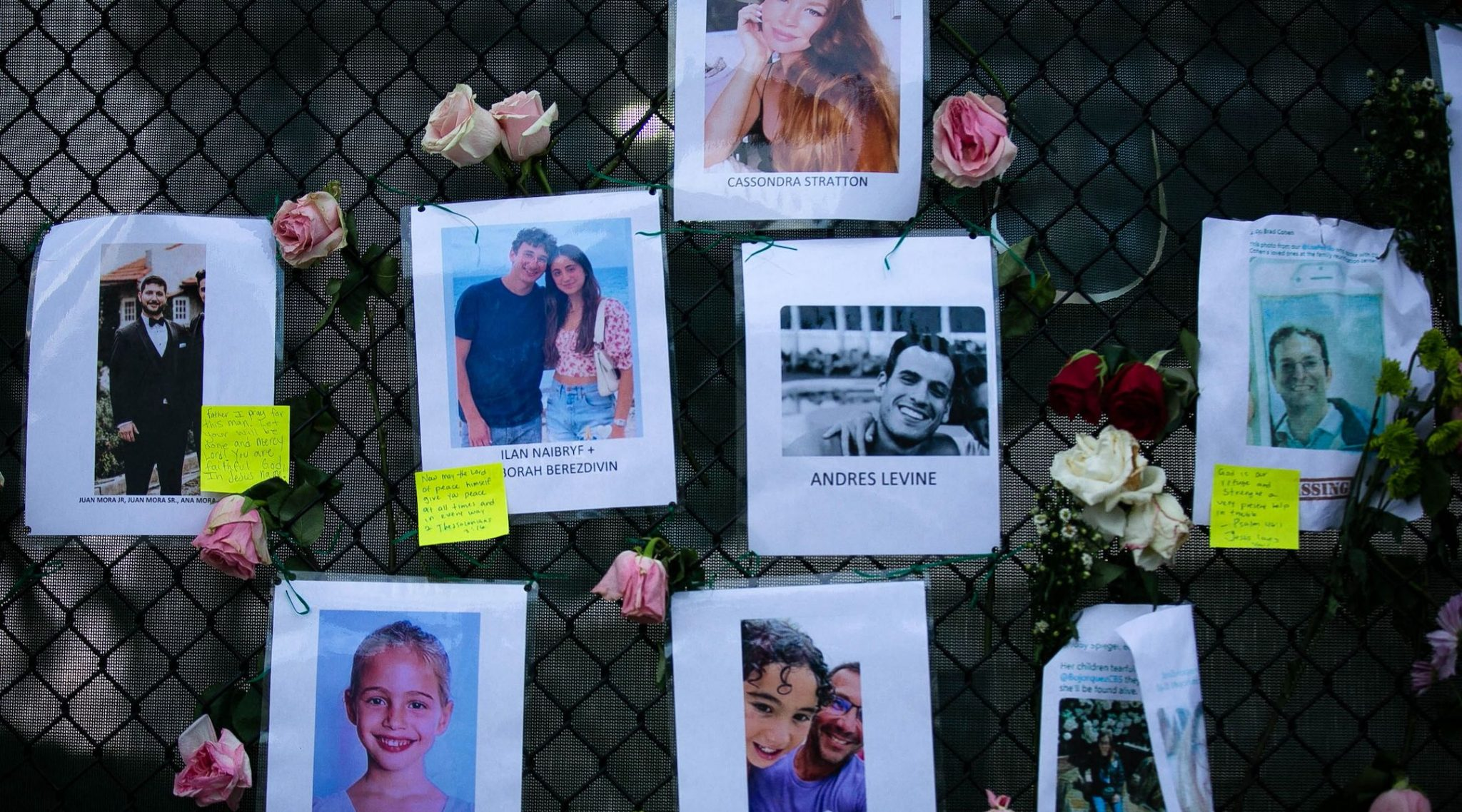 Images of Andres Levine, Ilan Naibryf and Deborah Berezdivin, three of the Jewish victims of the Surfside building collapse, among other photographs of those missing posted at a makeshift memorial on the building site in Surfside, Florida, June 26, 2021. (Photo/JTA-Andrea Sarcos-AFP via Getty Images)