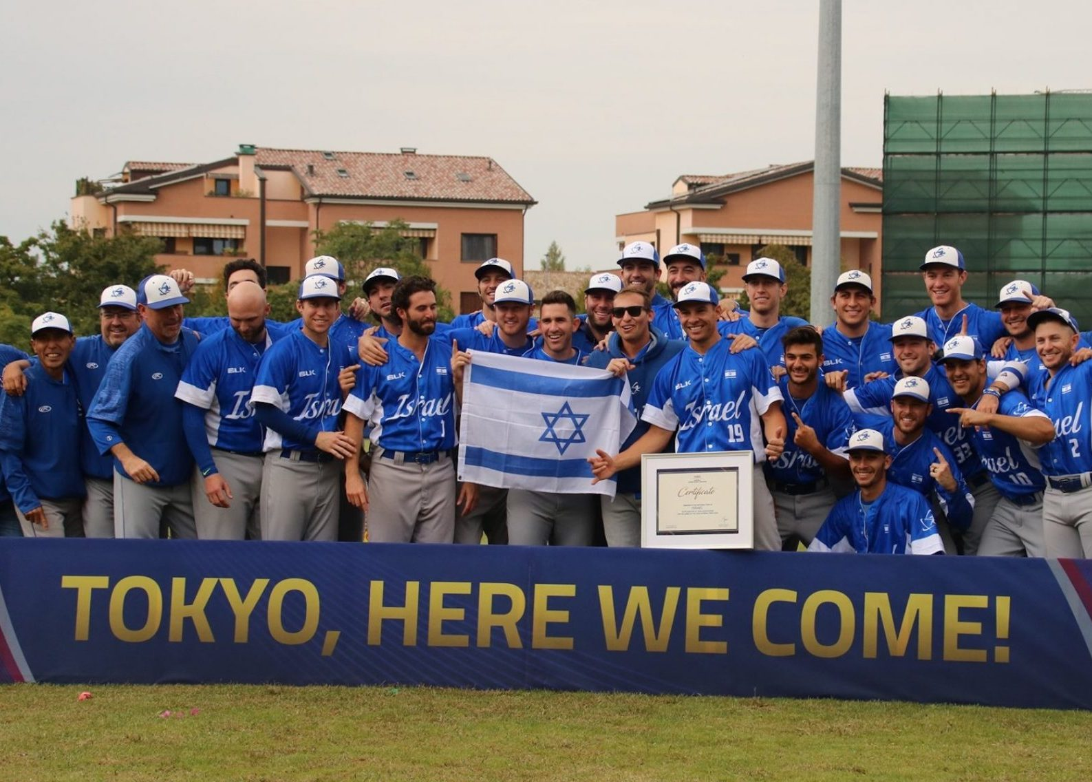 """players in their blue Israel baseball uniforms pose with a sign that reads, """"Tokyo, here we come!"""""""