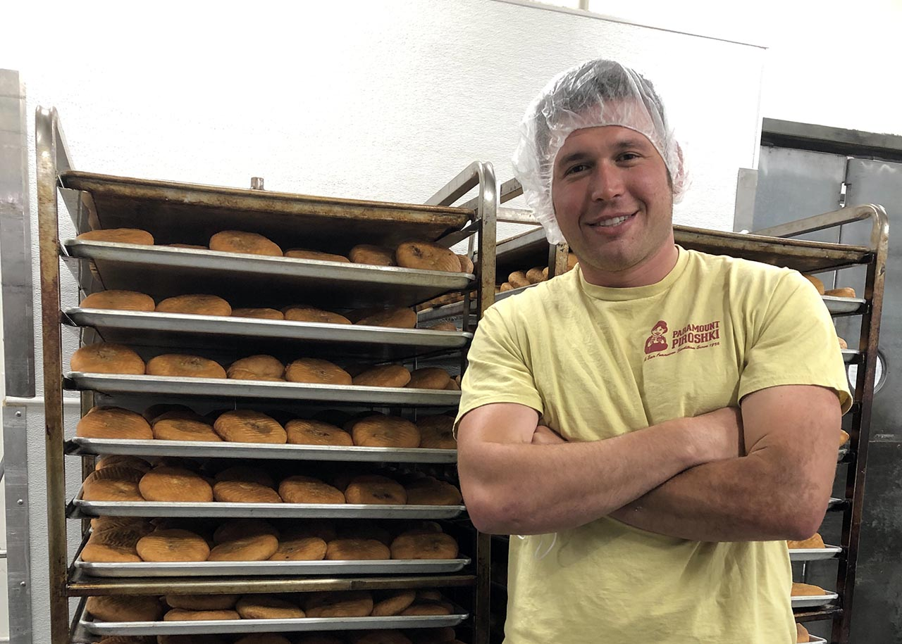 Josh Galant with trays of piroshki, the family business for 25 years. (Photo/Alix Wall)