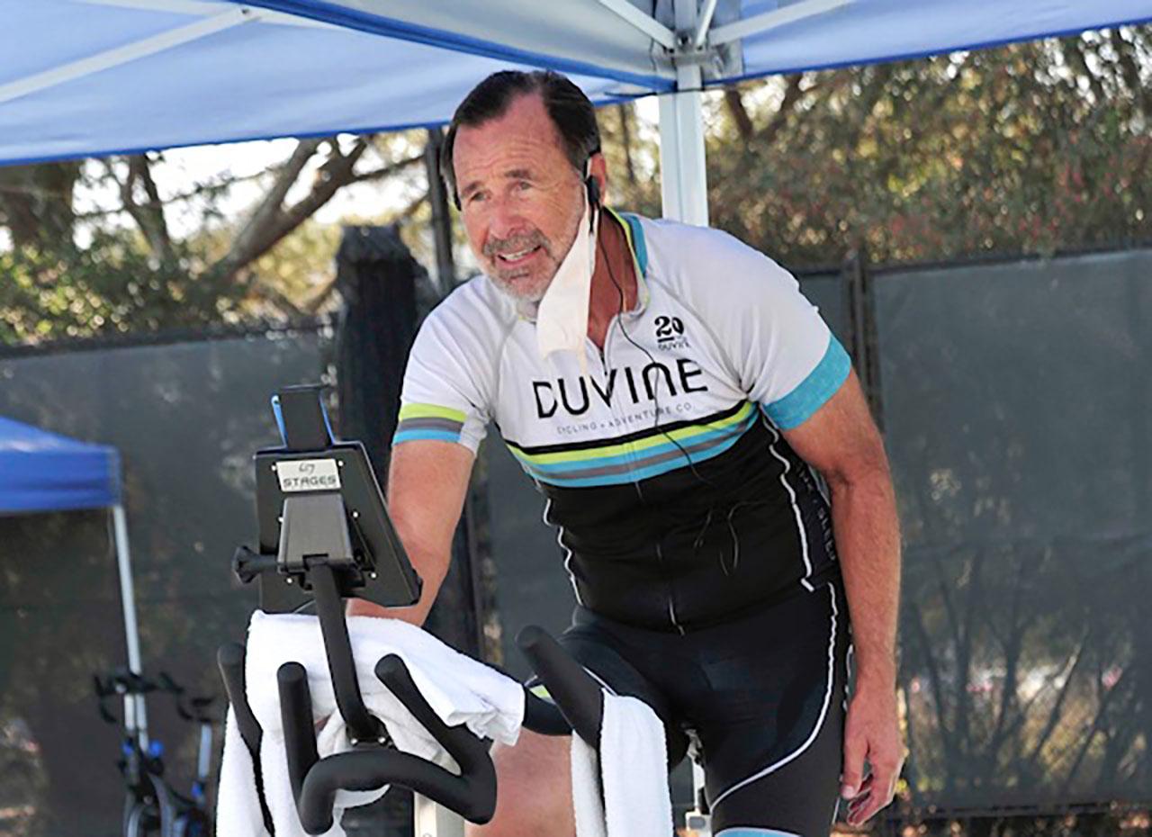 an older white man in biking garb atop an exercise bike