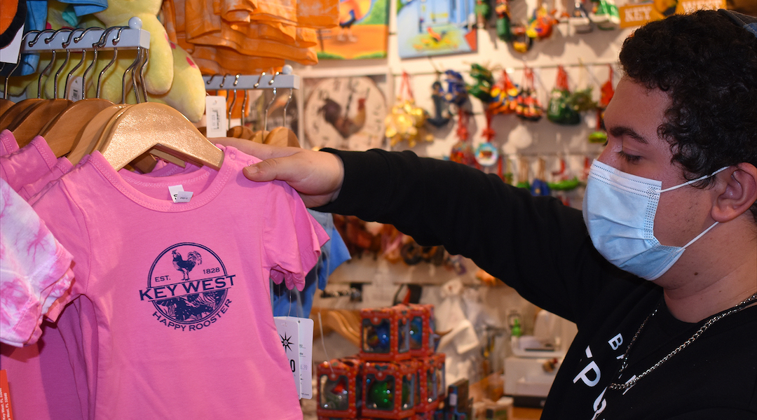 One of the only Jewish kids in Key West, Gili Sanouf, 17, sorts through T-shirts and beachwear at the souvenir shop owned by his parents. (Photo/Larry Luxner)