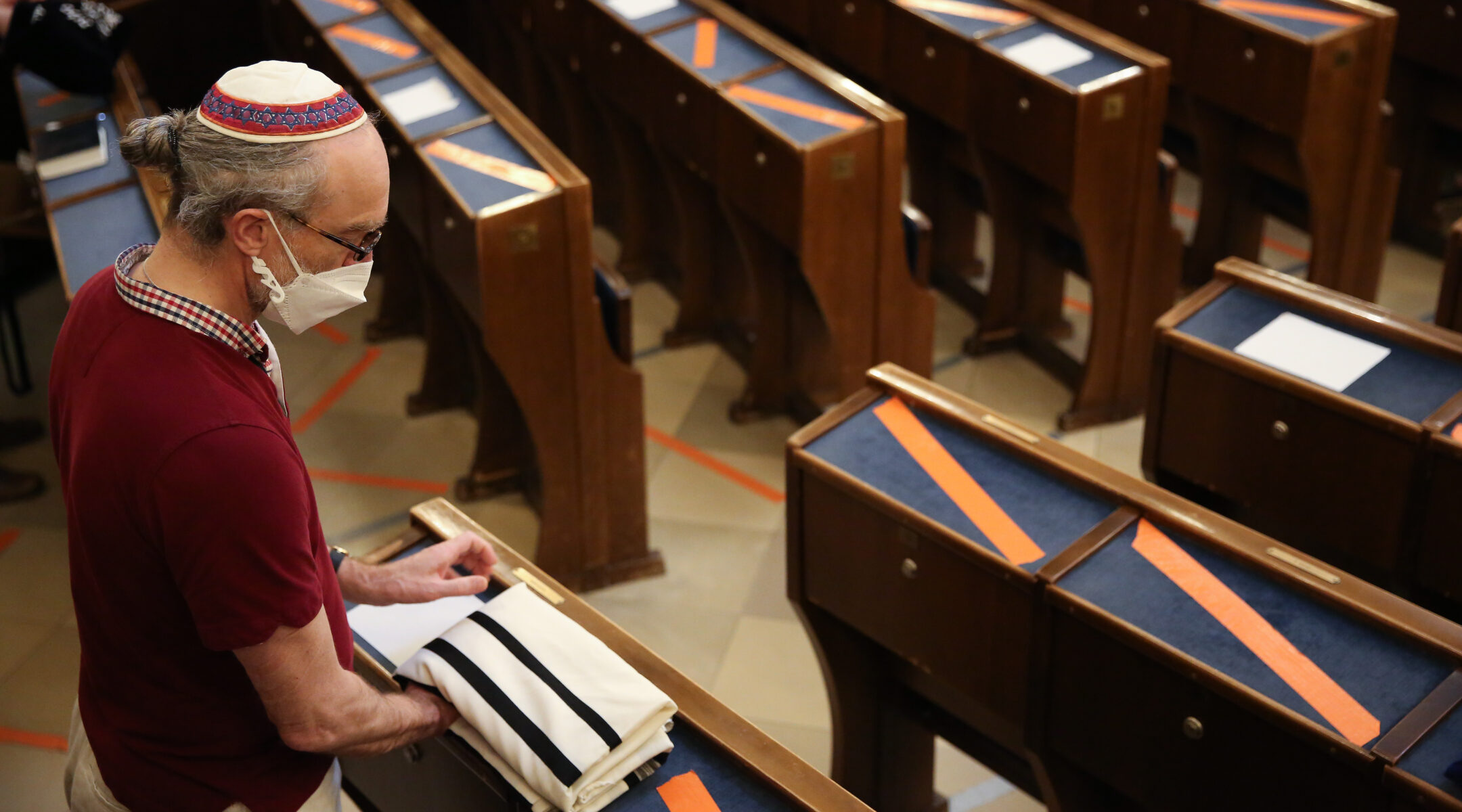 A synagogue-goer packs up his tallit, or prayer shawl, after services in Vienna, Austria, in July 2021. (Photo/JTA-Adam Berry-Getty Images)