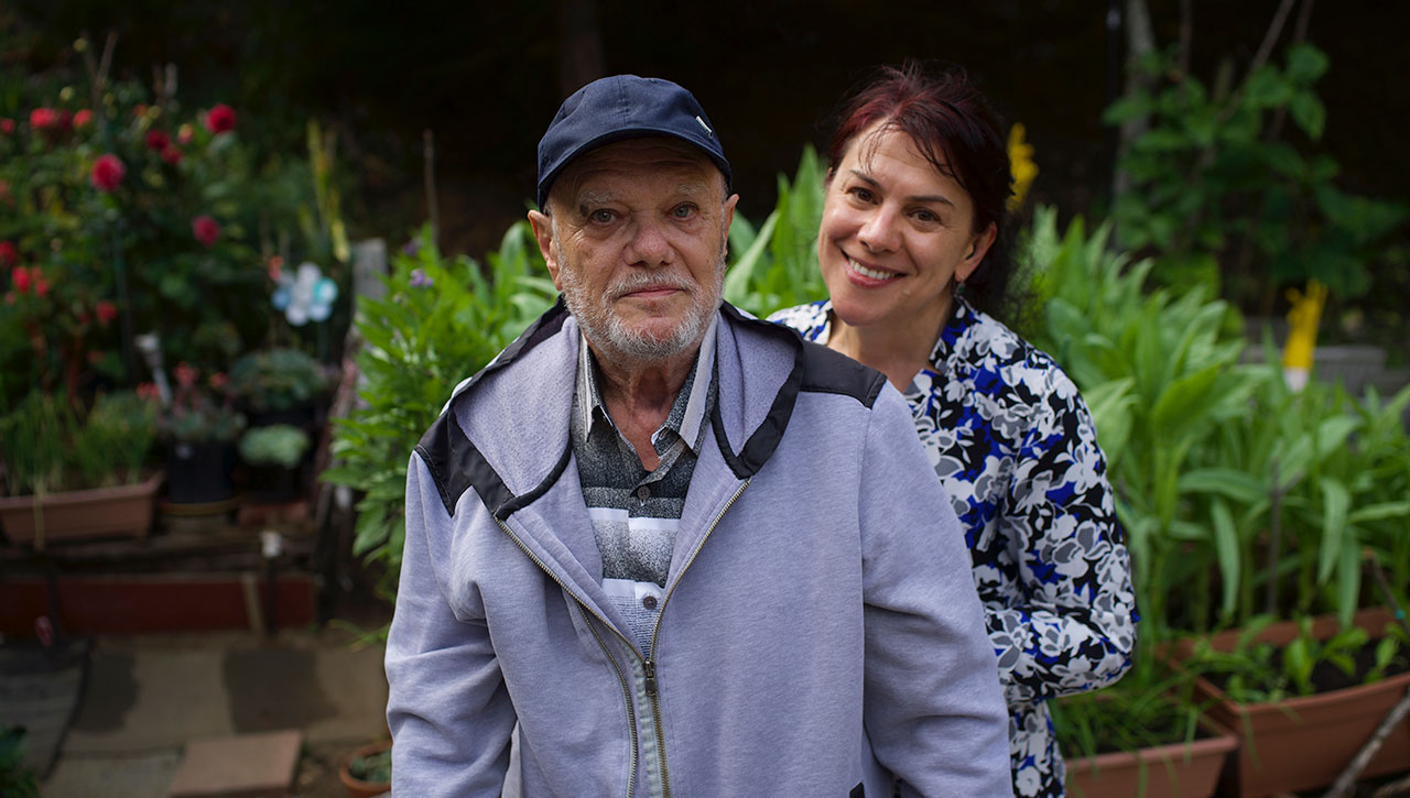 Vitali Voskoboinik stands with his daughter, Yulia Nedzvetski, in the garden of his home at Terrace Senior Housing in Pacifica. (Photo/Lea Loeb)