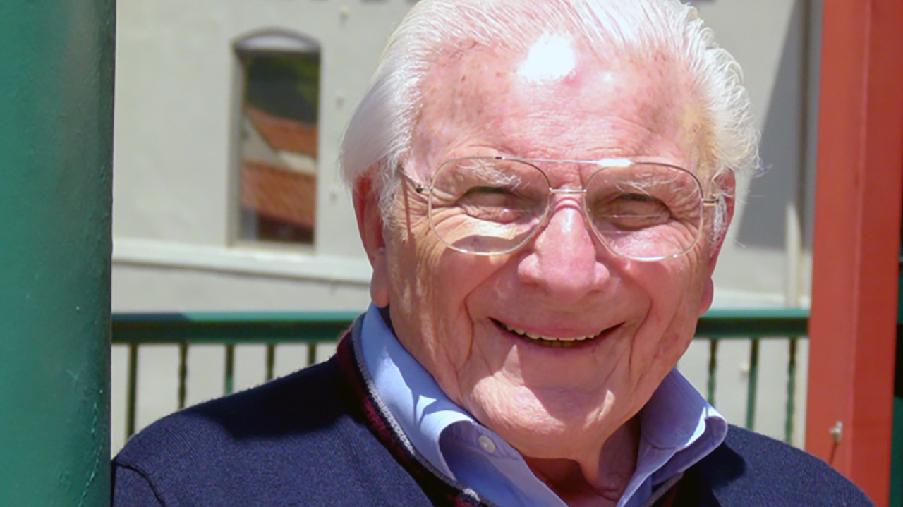 headshot of a smiling old man outside