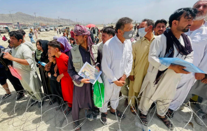 A man holds a certificate acknowledging his work for Americans (center) as hundreds of people gather outside the international airport in Kabul, Afghanistan, Aug. 17, 2021.  (Photo/RNS-AP)