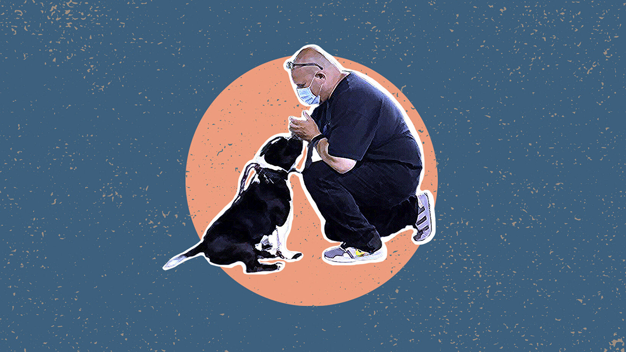 Jon Grobman kneels with a rescue dog that he is training as part of Paws for Life K9 Rescue, a nonprofit that brings dogs into prisons like the one where Grobman was incarcerated for 13 years. (Image/JTA-Grace Yagel; Photo/Courtesy Grobman)