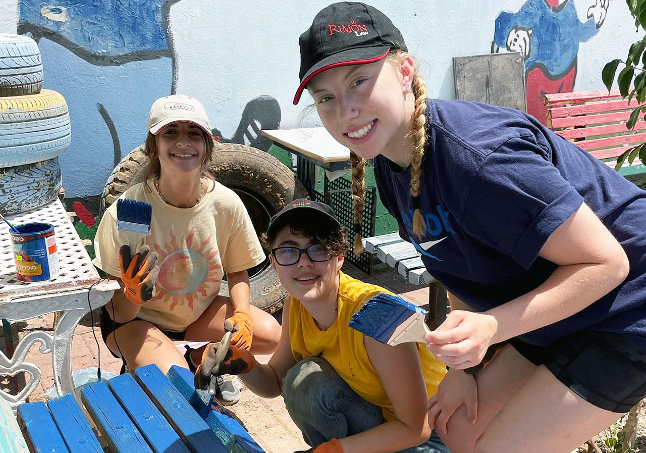 NorCal NCSY teens beautify a bench at a youth center in Kiryat Gat, Israel.