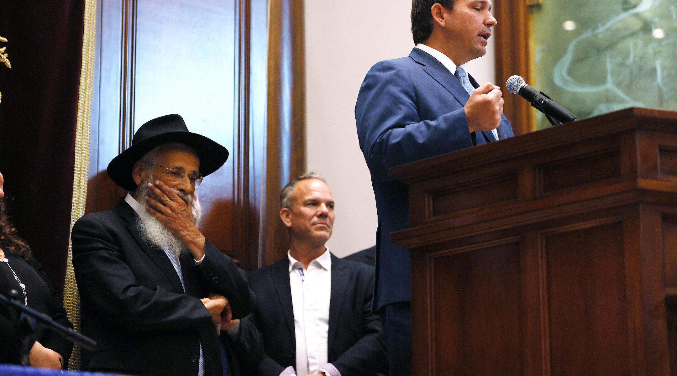 Rabbi Sholom Lipskar (left) listens as Florida Gov. Ron DeSantis speaks during a press conference at the Shul of Bal Harbour on June 14, 2021 in Surfside, Florida. (Photo/JTA-Joe Raedle-Getty Images)