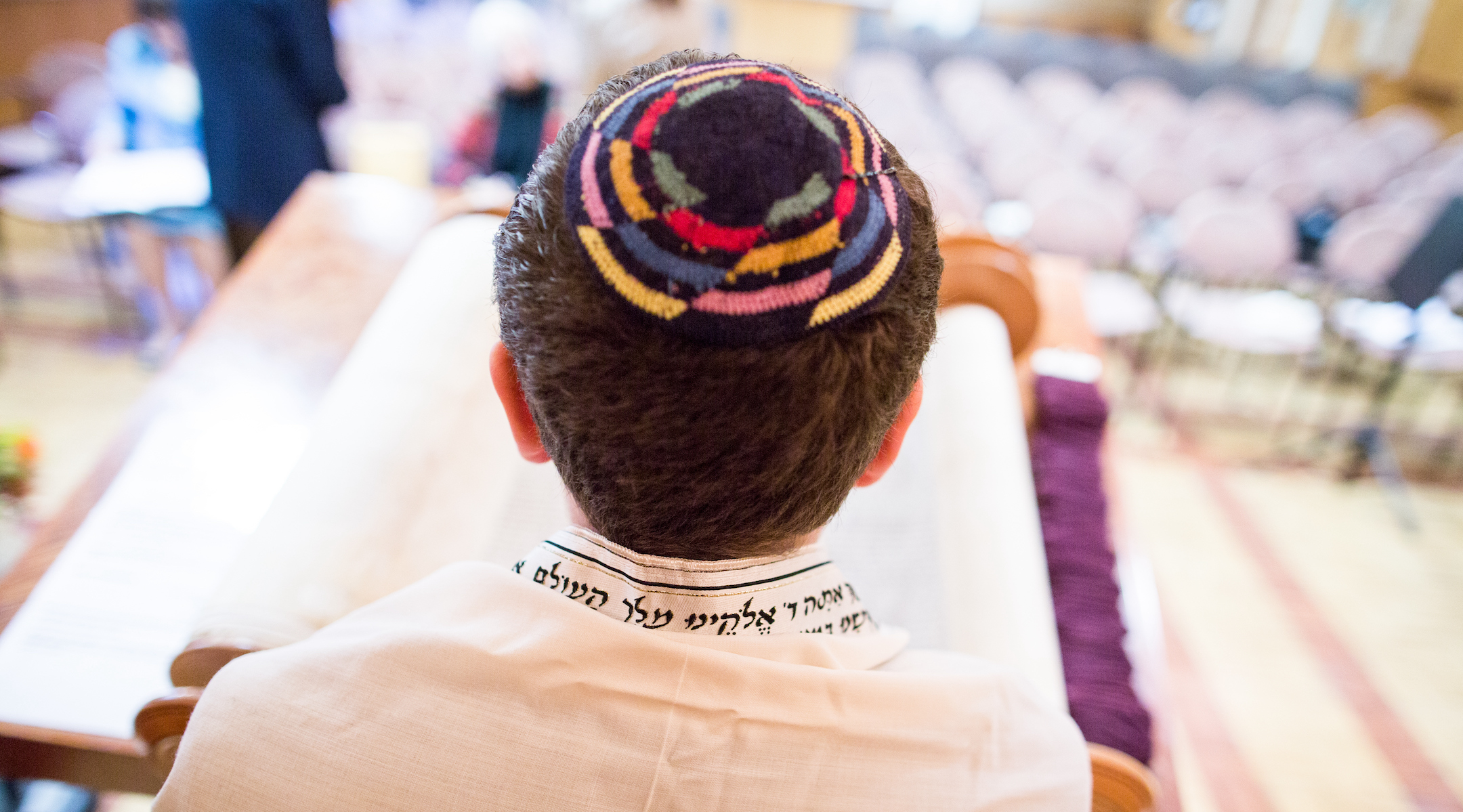 a man wearing a tallit and a colorful kippah seen from above in synagogue