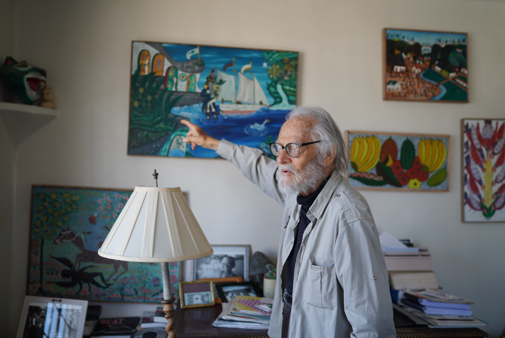 Herbert Gold points to a painting he got in Haiti. (Photo/George Barahona)