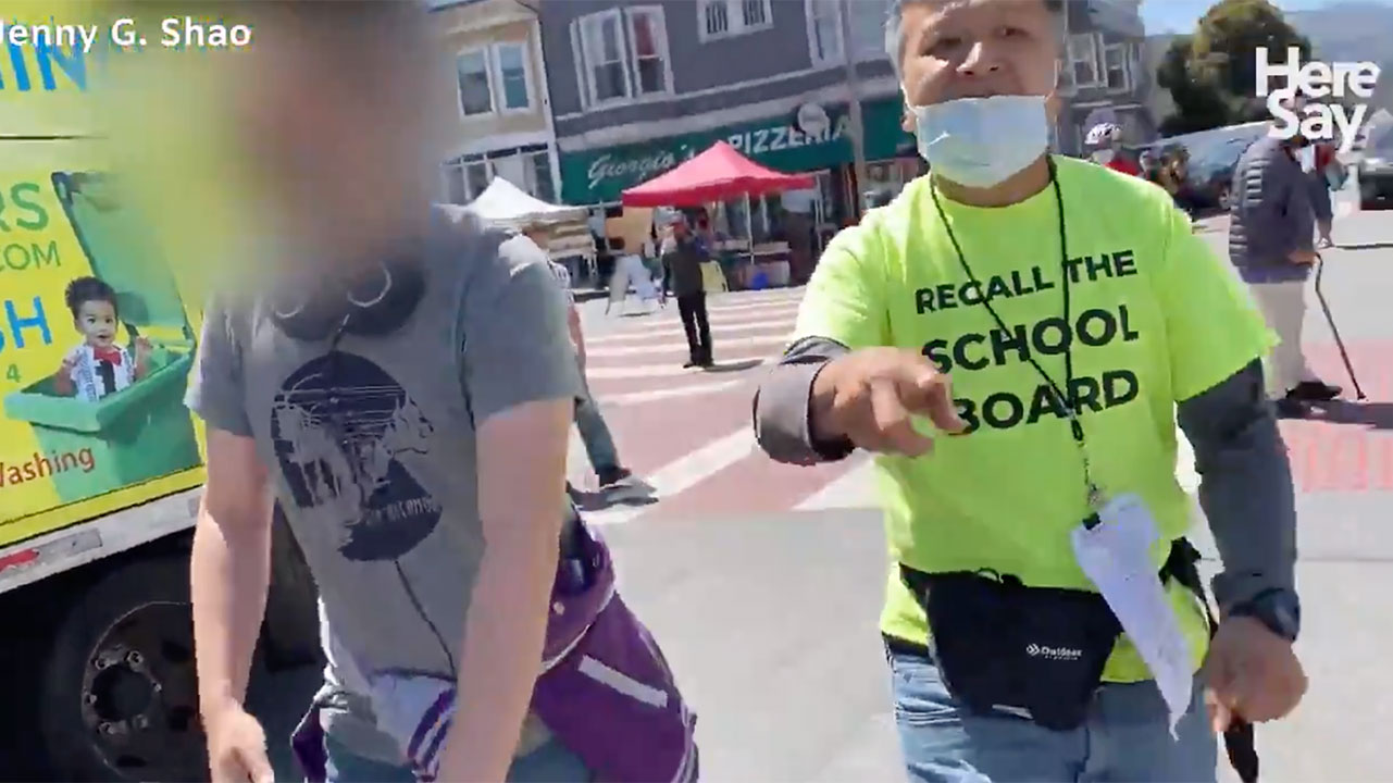 Screenshot from a video posted on Twitter in June that allegedly shows a former JVS employee (left) stealing a school board recall petition from a volunteer collecting signatures (right) in San Francisco.