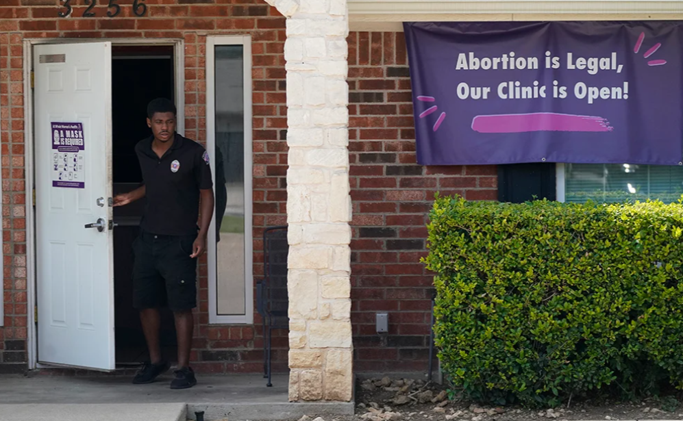 A security guard opens the door to the Whole Women's Health Clinic in Fort Worth, Texas. (Photo/RNS-AP-LM Otero)
