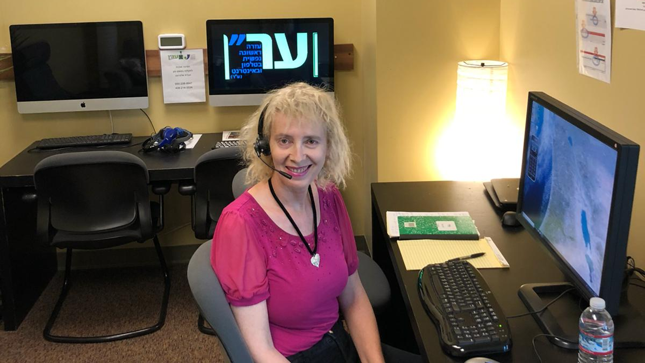 Nili Helman Caspi, an ERAN volunteer, sits at her desk where she answers calls to the hotline.