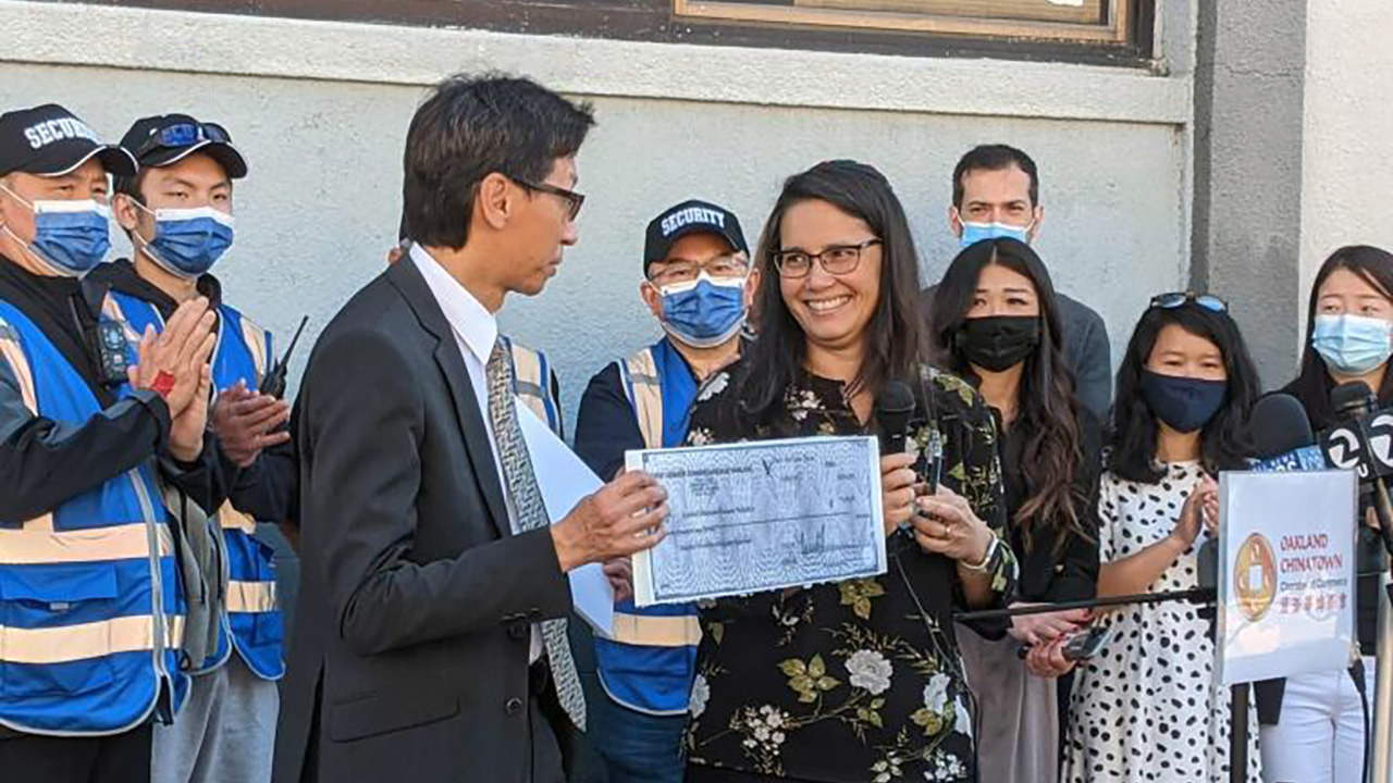 Rabbi Jacqueline Mates-Muchin of Temple Sinai presents Carl Chan, president of the Oakland Chinatown Chamber of Commerce, with money to help pay for security cameras in the neighborhood.