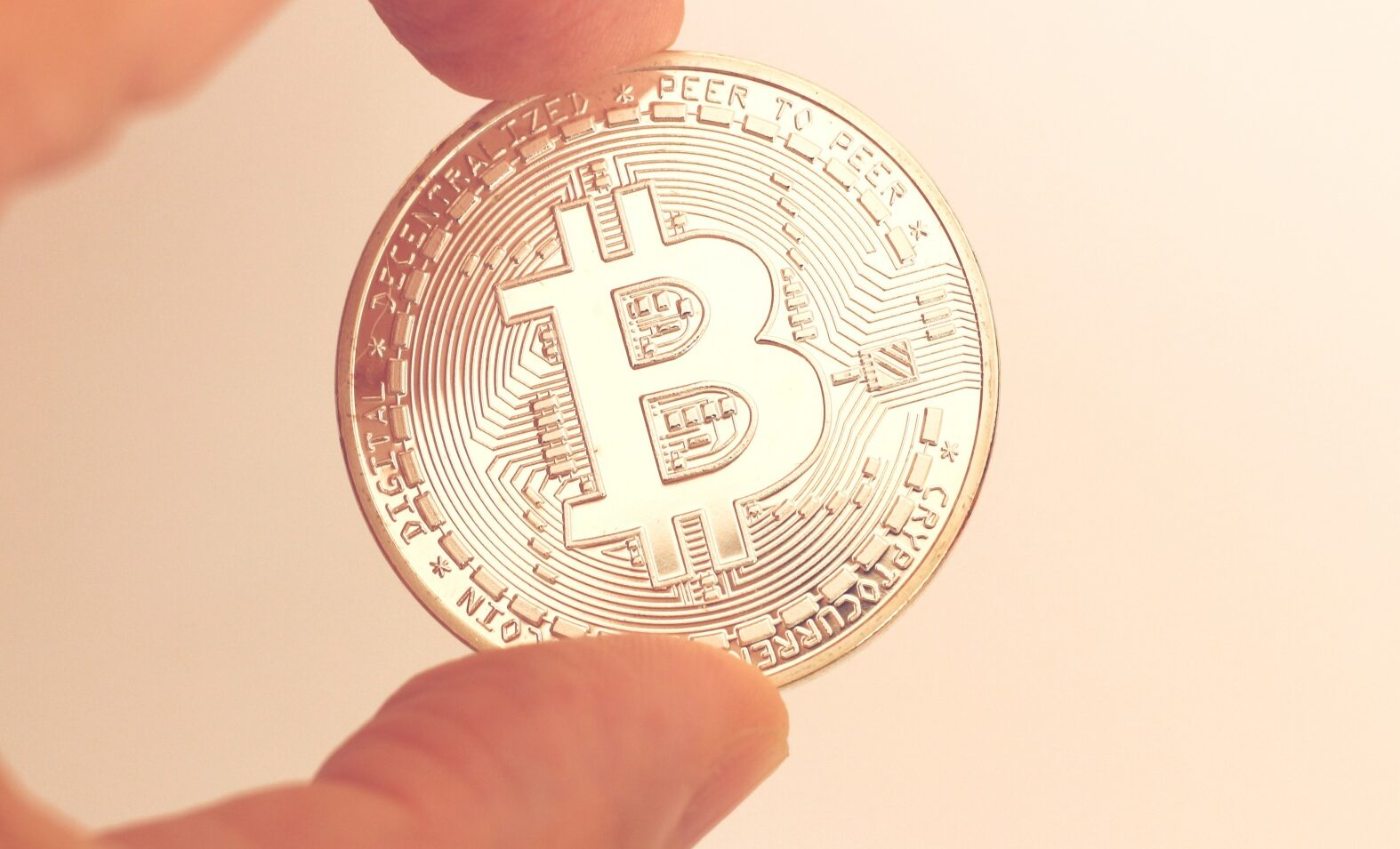 a gold physical bitcoin held between two fingers
